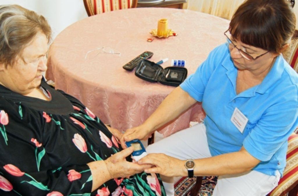 Die Zeit, die Karin Gimber (rechts) von der Diakonie Sillenbuch braucht, um einer Patientin ein Blutzuckermessgerät zu erklären, finanzieren die Krankenpflegevereine. Foto: Simone Bürkle