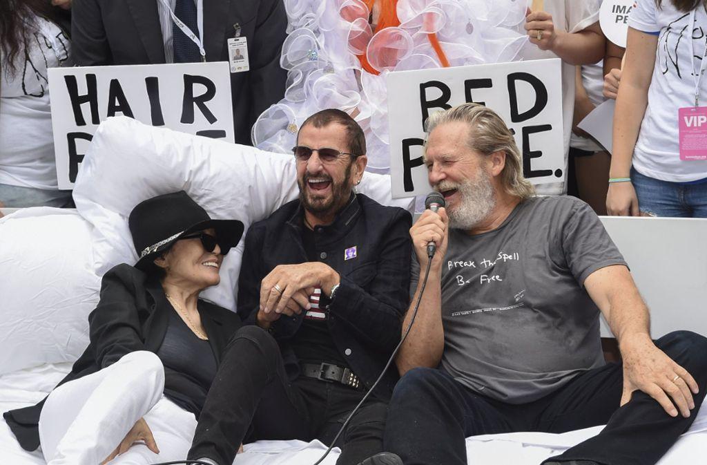 Anstelle von John Lennon traten sein ehemaliger Beatles-Kollege Ringo Starr (Mitte) und Oskar-Preisträger Jeff Bridges zur Aktion an und ließen sich mit Yoko Ono ablichten. Foto: Invision/AP