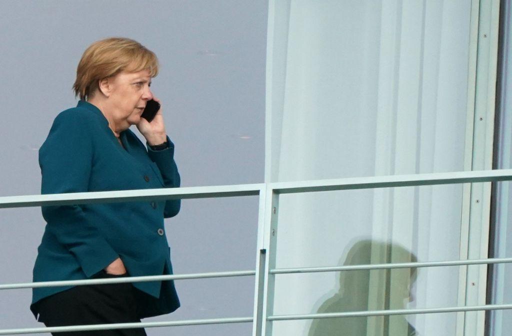 Angela Merkel telefoniert kurz vor der endgültigen Entscheidung auf dem Balkon des Kanzlerapartments – insgesamt hat sie sich fast 19 Stunden am Stück mit ihrer Koalition beraten. Foto: dpa/Kay Nietfeld