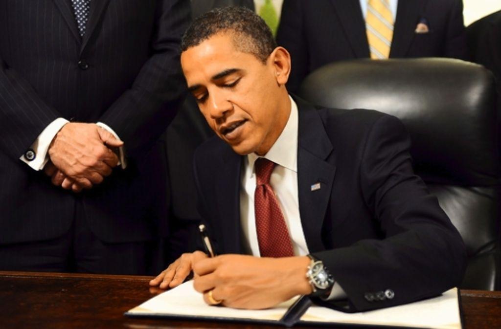 US-Präsident Barack Obama  unterzeichnet mit links. Foto: dpa