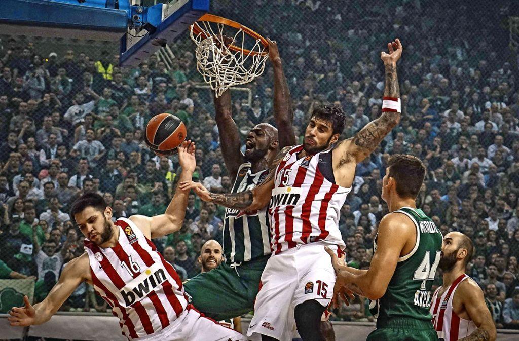 James Gist (Mi., grünes Trikot) setzt sich gegen Olympiakos unterm Korb kraftvoll durch. Foto: imago/Giannis Alexopoulos