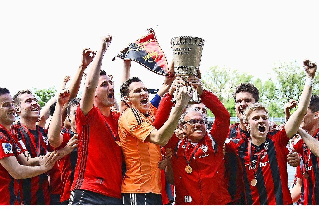 Das ist der Pott: Trainer Helmut Dietterle (mit Pokal) und die SF Dorfmerkingen feiern den WFV-Pokal-Sieg. Foto: Baumann