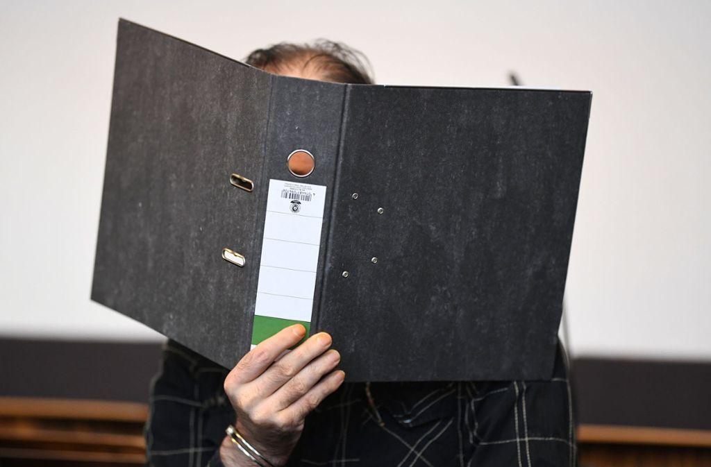 Der wegen Kindesmissbrauchs angeklagte Jürgen W. aus der Schweiz sitzt mit einem Ordner vor dem Gesicht in einem Saal des Landgerichts. Foto: dpa