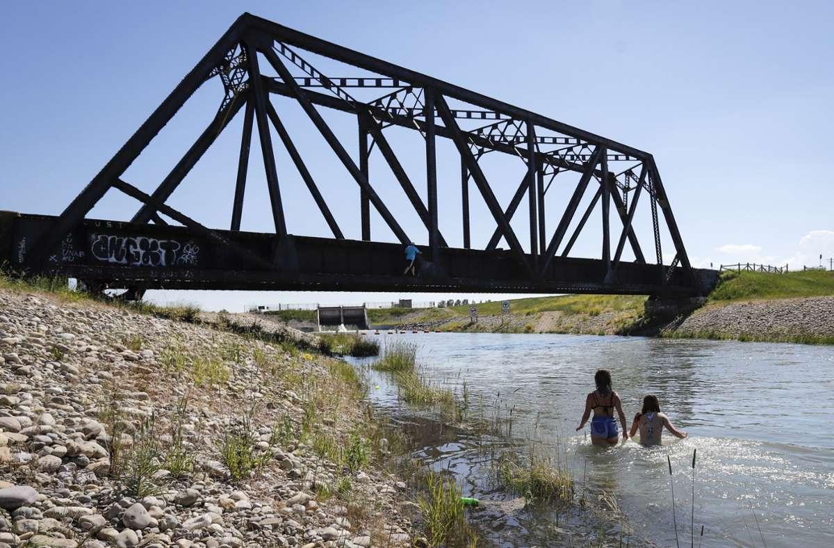 Junge Leute kühlen sich in einem Bewässerungskanal ab. Die anhaltende Hitzewelle im Westen Kanadas hat für neue Höchsttemperaturen gesorgt und zu mehreren Todesfällen beigetragen. Foto: dpa/Jeff Mcintosh