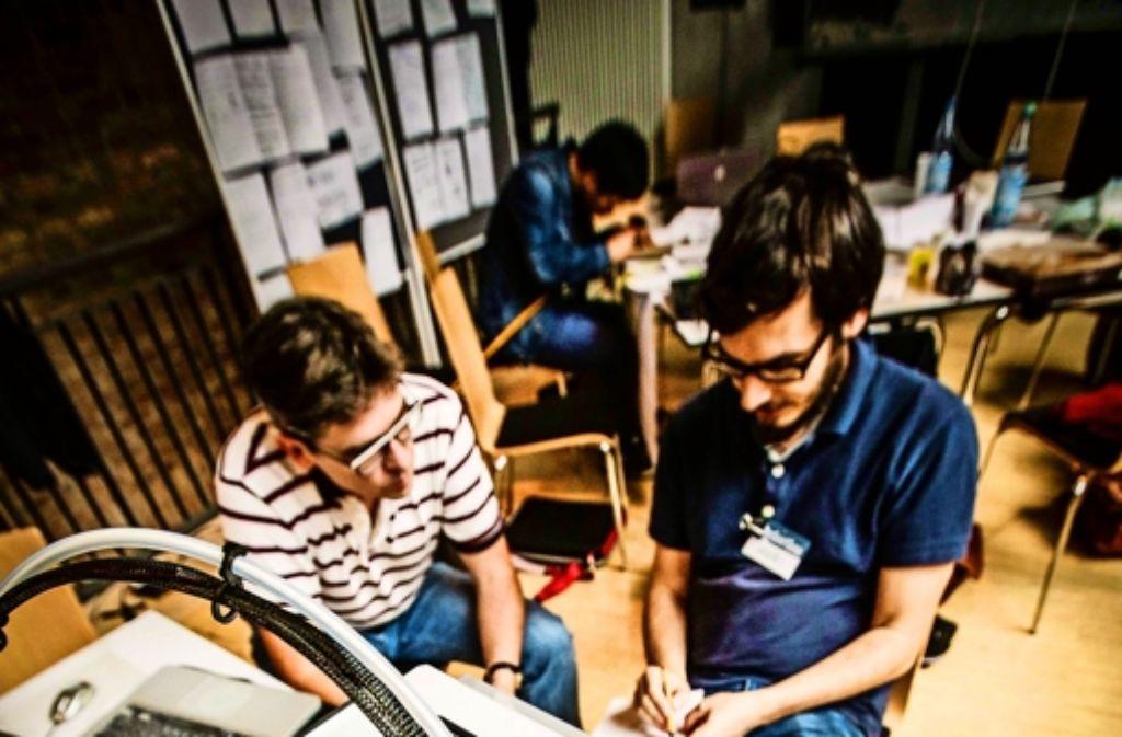 Matthias Riedel   (links) arbeitet an einem Sprachtelegrafen, während der 3-D-Drucker für eine andere Gruppe ein Brillenmodell produziert. Foto: Lichtgut/Leif Piechowski