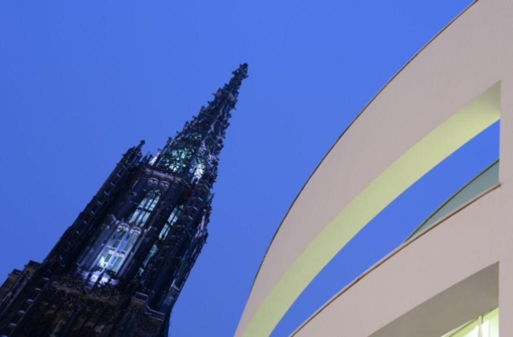 Der Turm des Münsters in Ulm – im  Vordergrund ist das weiße Stadthaus mit seiner besonderen Architektur zu sehen. Foto: dpa
