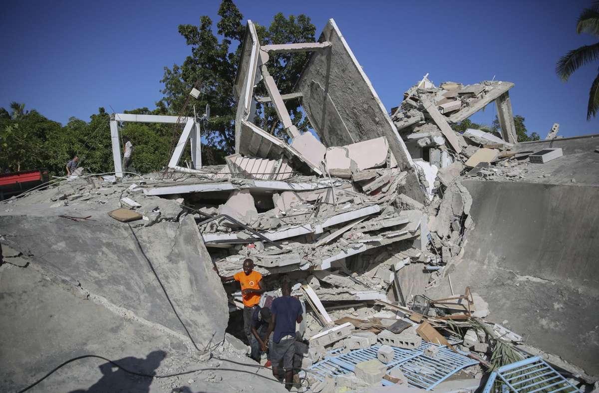 Menschen suchen nach dem Erdbeben  nach Überlebenden in einem zerstörten Haus. Foto: dpa/Joseph Odelyn