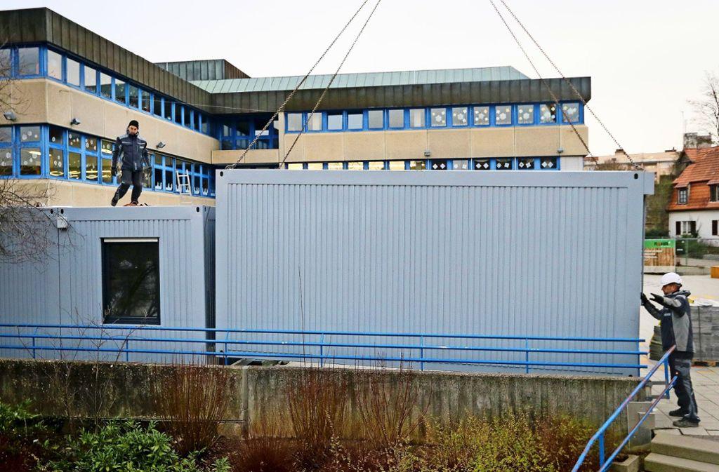 Zentimetergenau platzieren die Bauarbeiter den Container auf dem Schulhof. Foto: factum/Granville