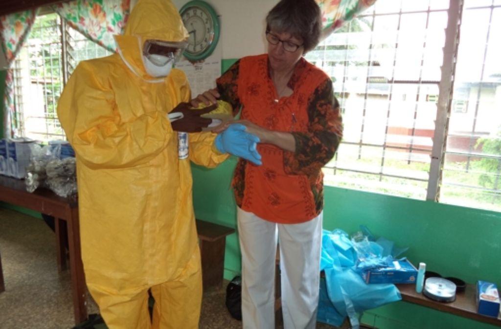 Die Tübinger Ärztin Gisela Schneider erläutert in einem Dorf in Liberia den korrekten Umgang mit den Schutzanzügen, die im Kampf gegen Ebola unerlässlich sind. Foto: Kremer