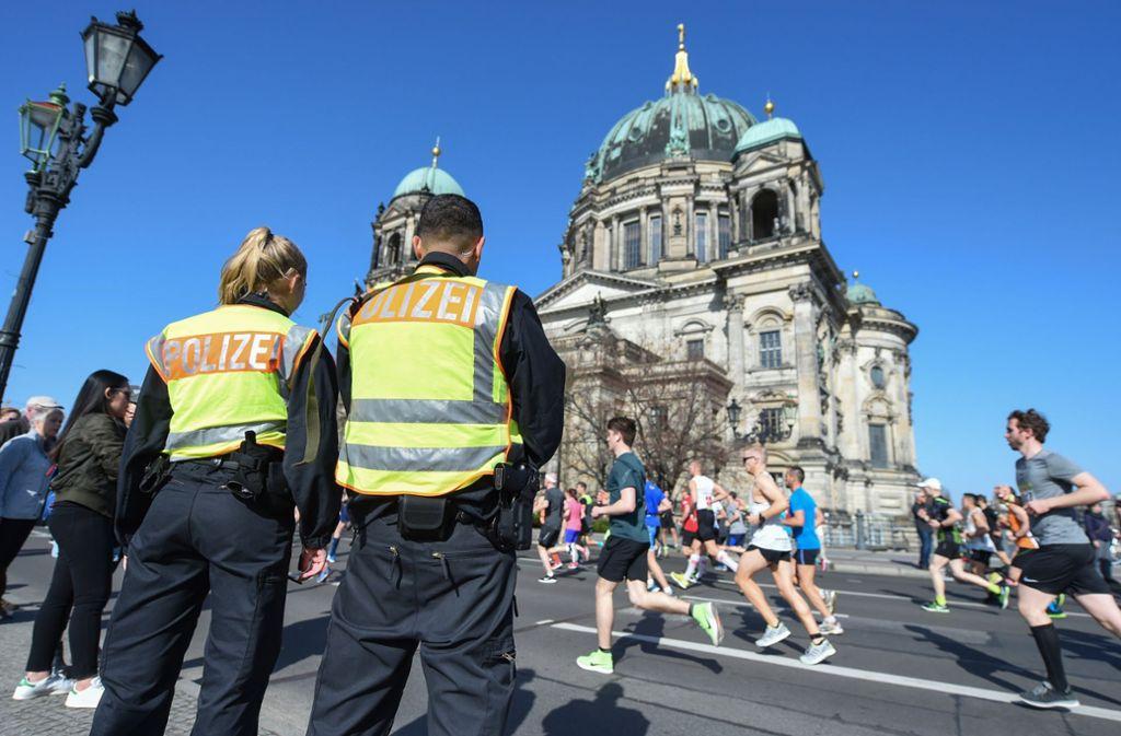 Zwei Polizisten stehen an der Halbmarathonstrecke in Berlin vor dem Dom. Foto: dpa