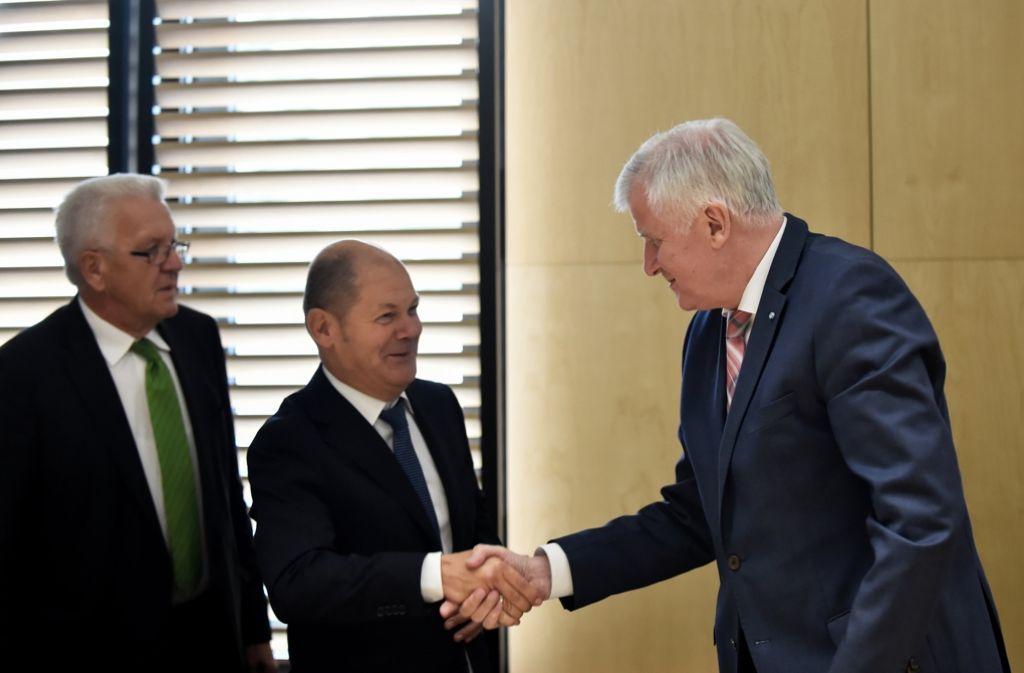 Der Erste Bürgermeister von Hamburg, Olaf Scholz (2.v.l., SPD) begrüßt im Bundesrat den Ministerpräsidenten des Freistaates Bayern, Horst Seehofer (rechts, CSU) im Vermittlungsausschuss. Neben den beiden Politikern steht der Ministerpräsident des Landes Baden-Württembergs, Winfried Kretschmann (links, Bündnis 90/Die Grünen). Der Vermittlungsausschuss von Bundestag und -rat hat sich am Mittwochabend Teilnehmern zufolge auf eine Reform der Erbschaftsteuer geeinigt. Foto: dpa