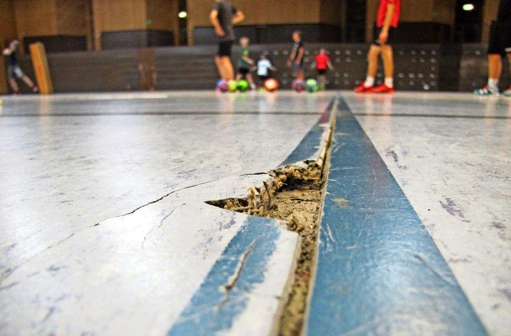 Das Loch hinter dem Tor ist nicht das einzige in der Halle. Da sich die Kunststoffbahnen des Bodens lösen, entstehen überall Risse. Die Vereine flicken diese provisorisch. Foto: Eileen Breuer