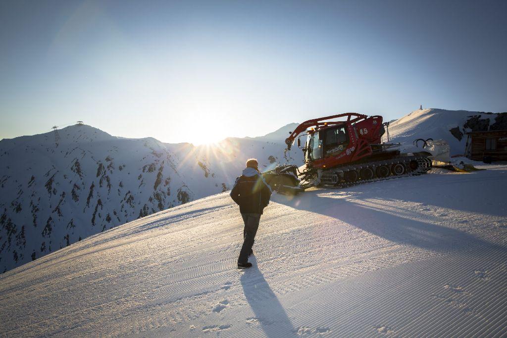Wenn die Sonne hinter den Zillertaler Bergen verschwindet, beginnt der Arbeitstag für die Männer der Pistenpräparierung.  Foto: Zillertaltourismus/Julia Rotter