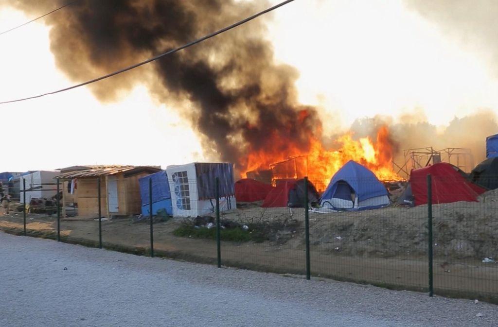 Rauch steigt über dem Flüchtlingslager in Calais in Frankreich auf. Hier ist es zu einer gewaltsamen Auseinandersetzung zwischen Flüchtlingen gekommen. Foto: AP