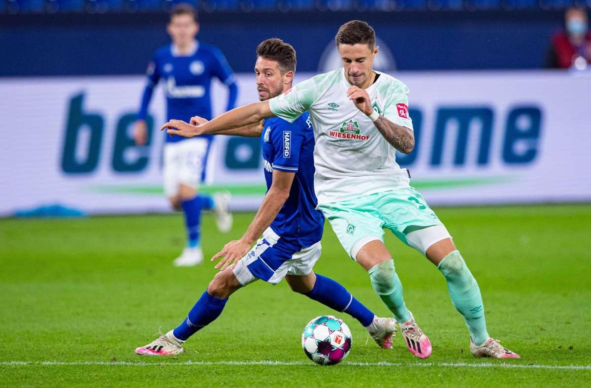 Mark Uth (l) und Bremens Marco Friedlb kämpfen um den Ball. Foto: dpa/Guido Kirchner