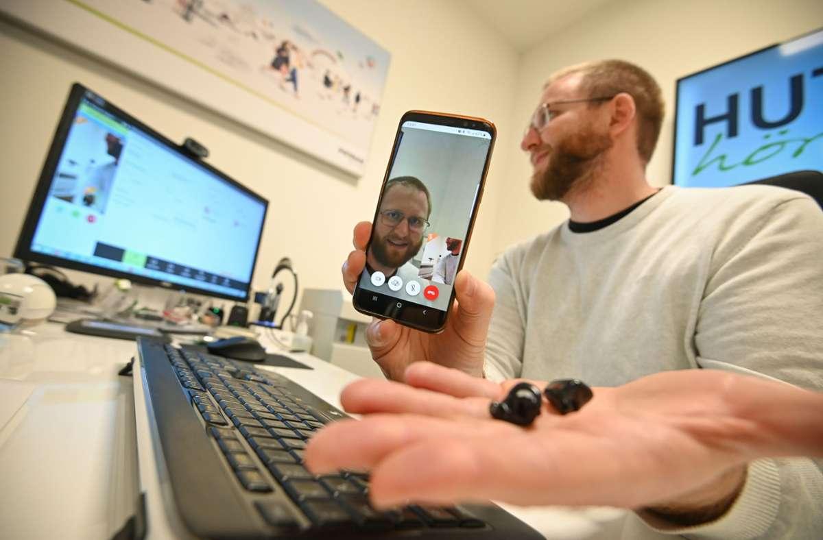 Simon Huth stellt Hörgeräte übers Handy des Kunden ein. Foto: Leif Piechowski/Leif Piechowski