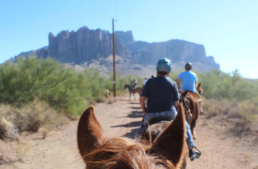 Reiten in der Sonora-Wüste von Arizona: Im Hintergrund türmt sich das mächtige Bergmassiv der Superstition Mountains auf. Foto: Susanne Hamann