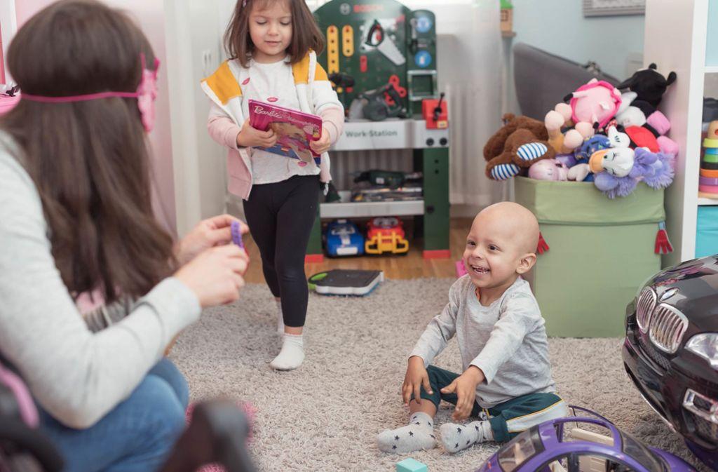 Michele lacht oft und gern – besonders beim Spiel mit seiner Schwester Mariella und Mutter Mariarosa. Foto: Lichtgut/Max Kovalenko