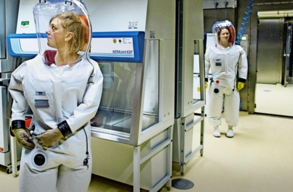 Wie auf einer Raumstation: Mitarbeiterinnen üben in zehn Kilogramm schweren Schutzanzügen die Laborarbeit. Foto: dpa