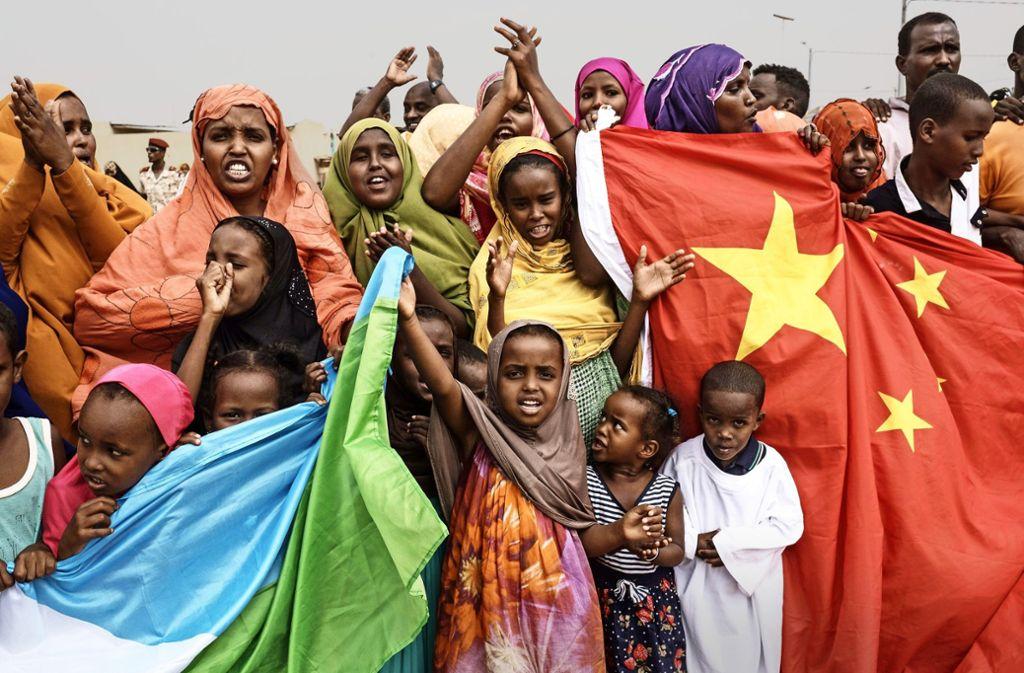 Einwohner feiern ein Bauprojekt mit den Flaggen Chinas und Dschibutis. Foto: AFP