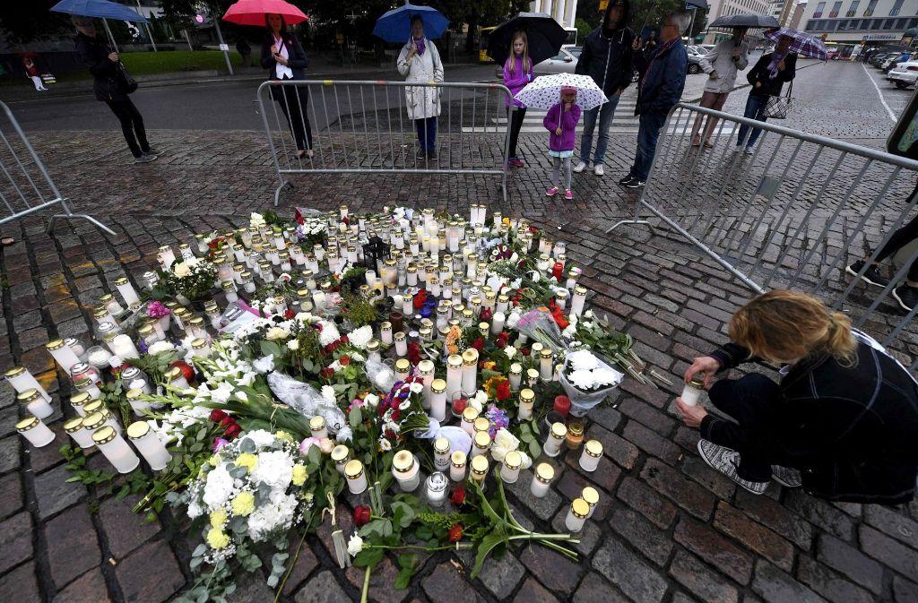 Menschen legen an der Stelle des Attentats in Turku Blumen und Kerzen nieder. Foto: AFP/Lehtikuva