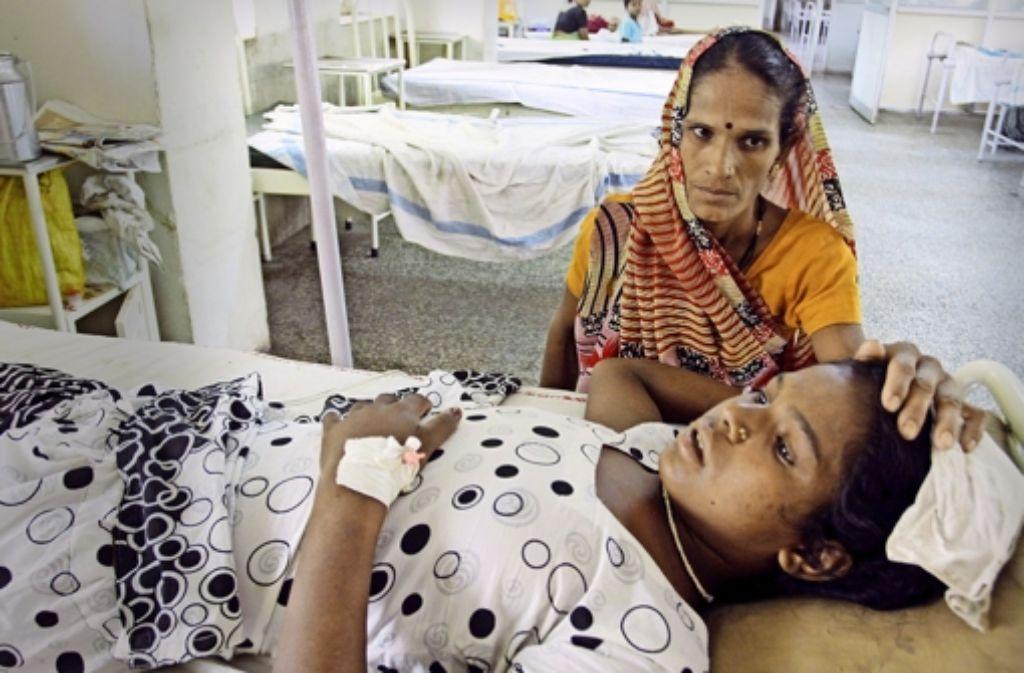 Ein Mädchen wird im Krankenhaus von Hamidia wegen Hitzschlag und Dehydration  versorgt (links). Weitere Bilder aus dem hitzegeplagten Indien zeigt die folgende Fotostrecke. Foto: AFP, dpa