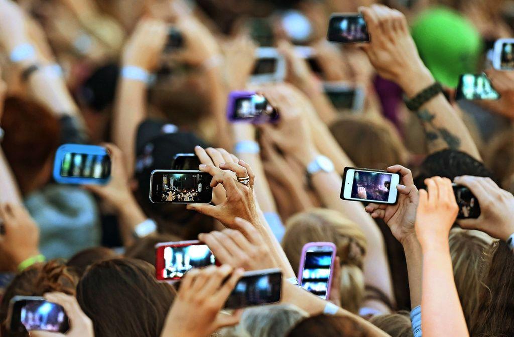 Smartphones sind im Dauereinsatz – so auch bei diesem Event. Foto: dpa