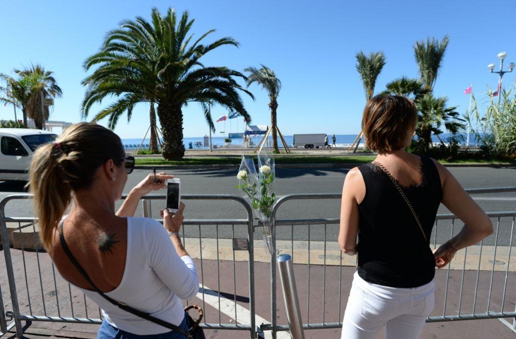 Eine Frau fotografiert die Rosen, die in die Absperrung an der Promenade in Nizza gesteckt wurden. Foto: dpa