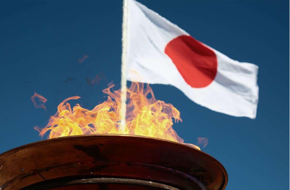 Das olympische Feuer brennt vor der Flagge Japans. Foto: imago//Markos Chouzouris
