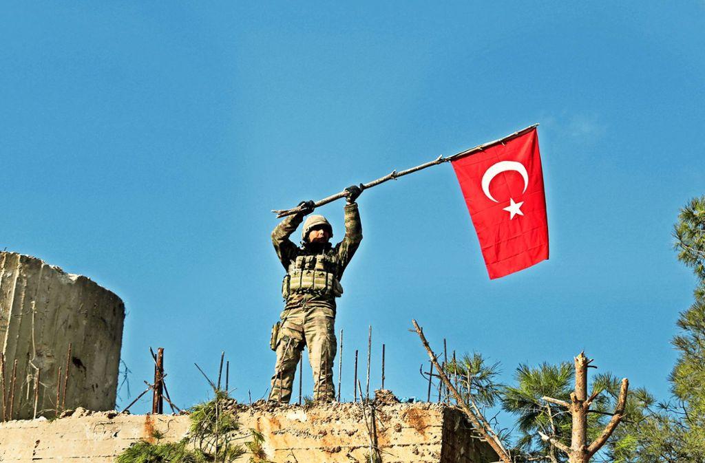 Ein Soldat schwenkt auf dem syrischen Berg Barsaja  eine türkische Flagge,  nachdem seine Armee das Gebiet erobert hat. Foto: AP