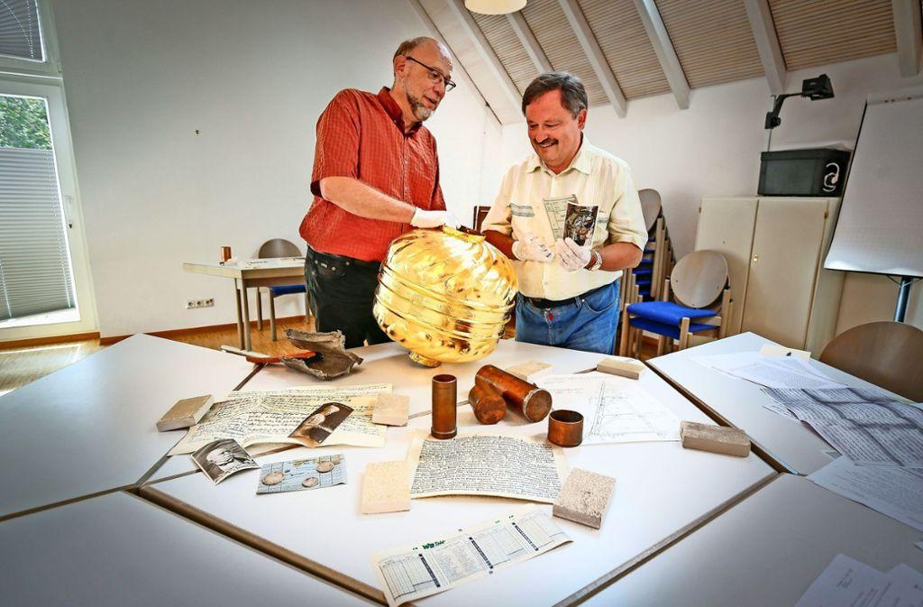 Pfarrer Jochen Helsen und Klaus Herrmann vom Stadtarchiv freuen sich über die vielen alten Dokumente. Die Kugel ist bereits wieder frisch vergoldet. Foto: factum/Granville