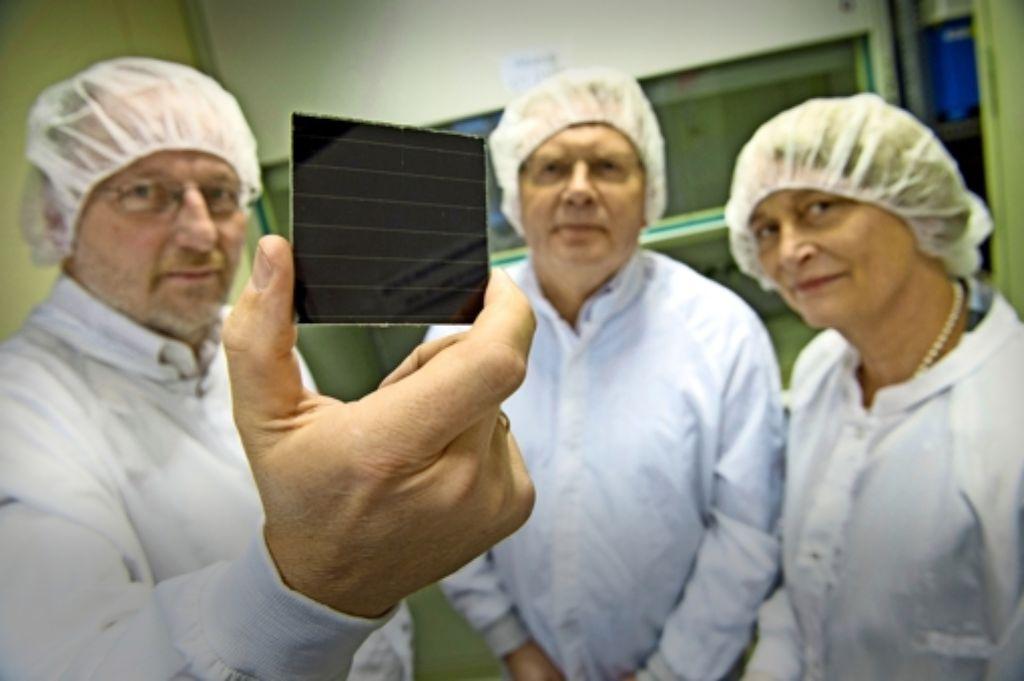 Michael Koch von der Uni Stuttgart hält ein Stück aus einem Solarmodul in der Hand, neben ihm stehen Jürgen Werner und Renate Zapf-Gottwick. Foto: dpa