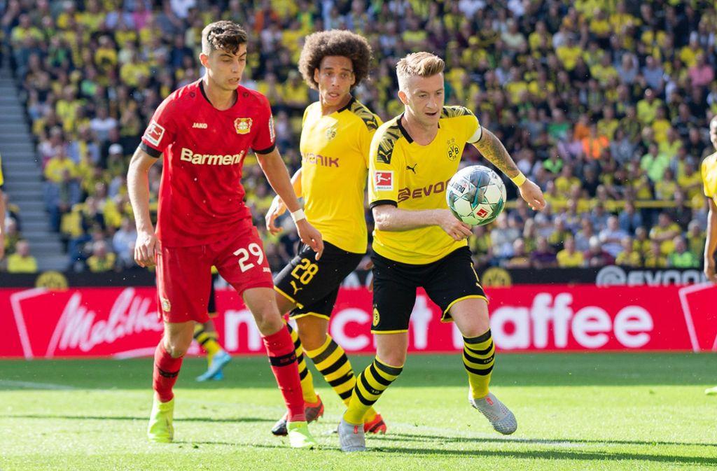 Marco Reus (rechts) von Borussia Dortmund zischt Leverkusens Kai Havertz (links) mit dem Ball davon. Foto: dpa/Marcel Kusch