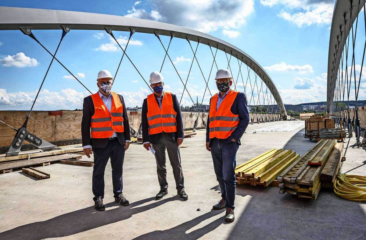 SSB-Chef Thomas Moser, Esslingens Landrat Heinz Eininger und Verkehrsminister Winfried Hermann (von links) vorschriftsmäßig maskiert auf der Stadtbahnbrücke über die A8 Foto: Lichtgut/Julian Rettig