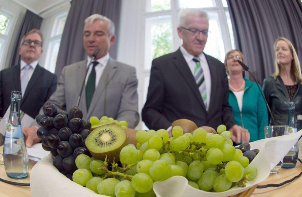 Mehr Symbolik geht nicht: Die Herren Strobl und Kretschmann in der Mitte, hinter grün-schwarzem Obst. Foto: dpa