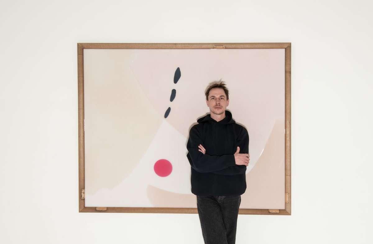 Thomas Lempertz steht in der Ausstellung in Sindelfingen vor einem Bild, das von ausgemusterten Ballettstangen gerahmt wird. Die Stangen stammen aus der alten Cranko-Schule in Stuttgart. Foto: Oliver Kröning/Galerie der Stadt Sindelfingen