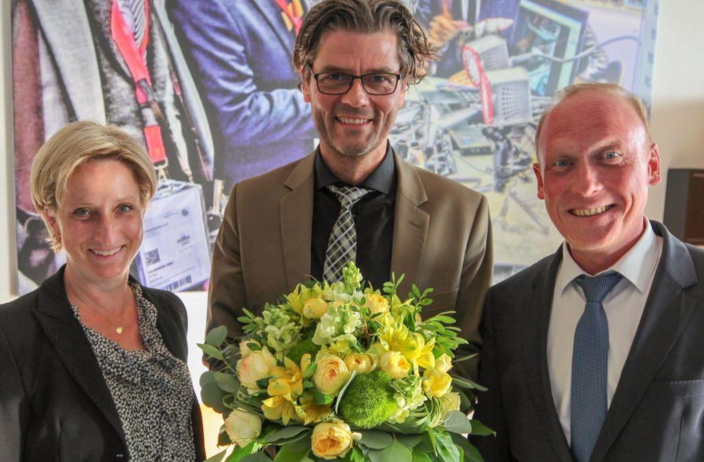 Der neue Messe-Chef Stefan Lohnert mit Blumen und mit zwei Gratulanten: Wirtschaftsministerin Nicole Hoffmeister-Kraut und Aufsichtsratschef Thomas Fuhrmann. Foto: Messe Stuttgart