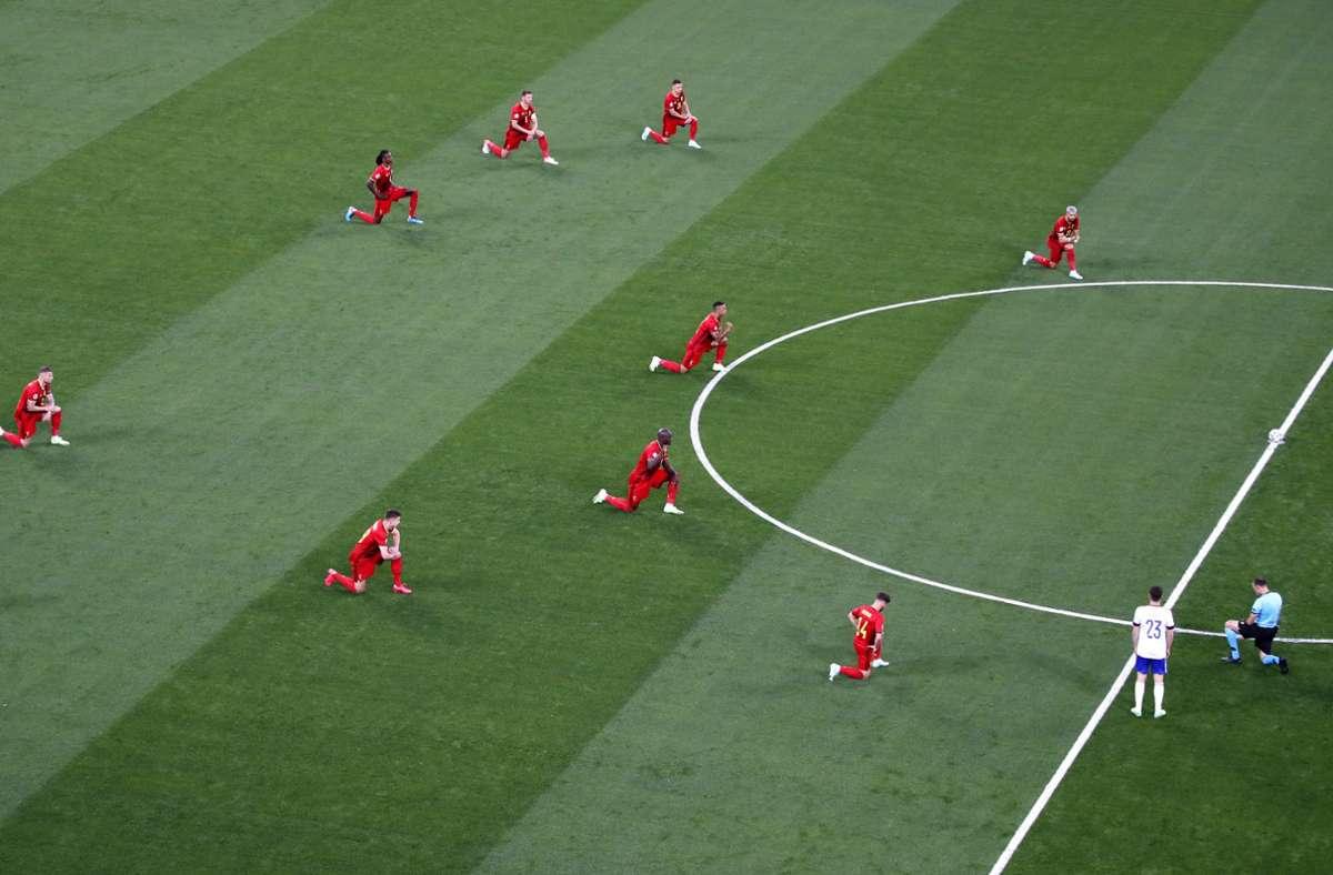 Die belgischen Spieler und der Schiedsrichter knien vor der Partie. Foto: dpa/Dmitry Lovetsky