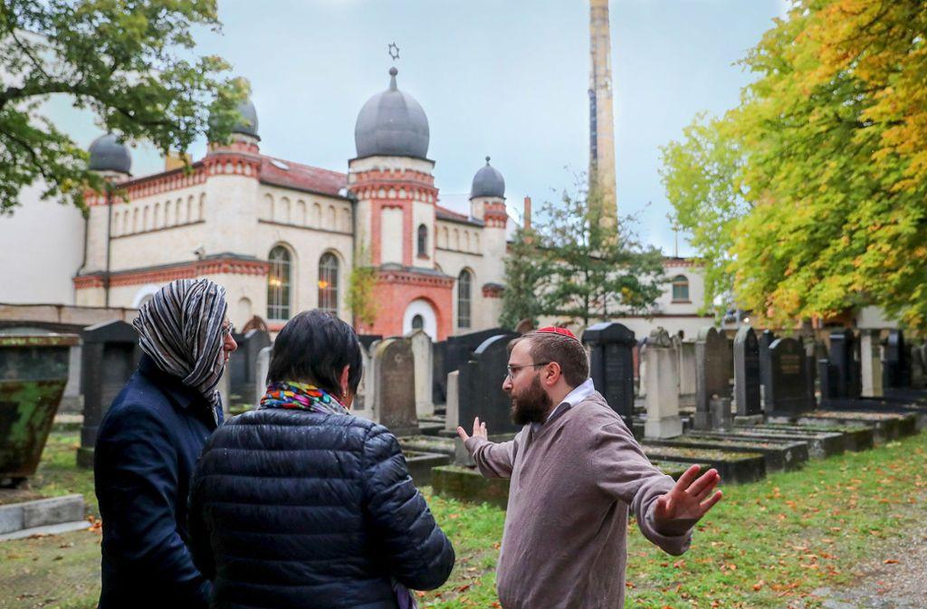 Mitglieder der Jüdischen Gemeinde  Halle unterhalten sich auf dem jüdischen Friedhof  mit einer Journalistin. Foto: dpa/Woitas, Gollnow