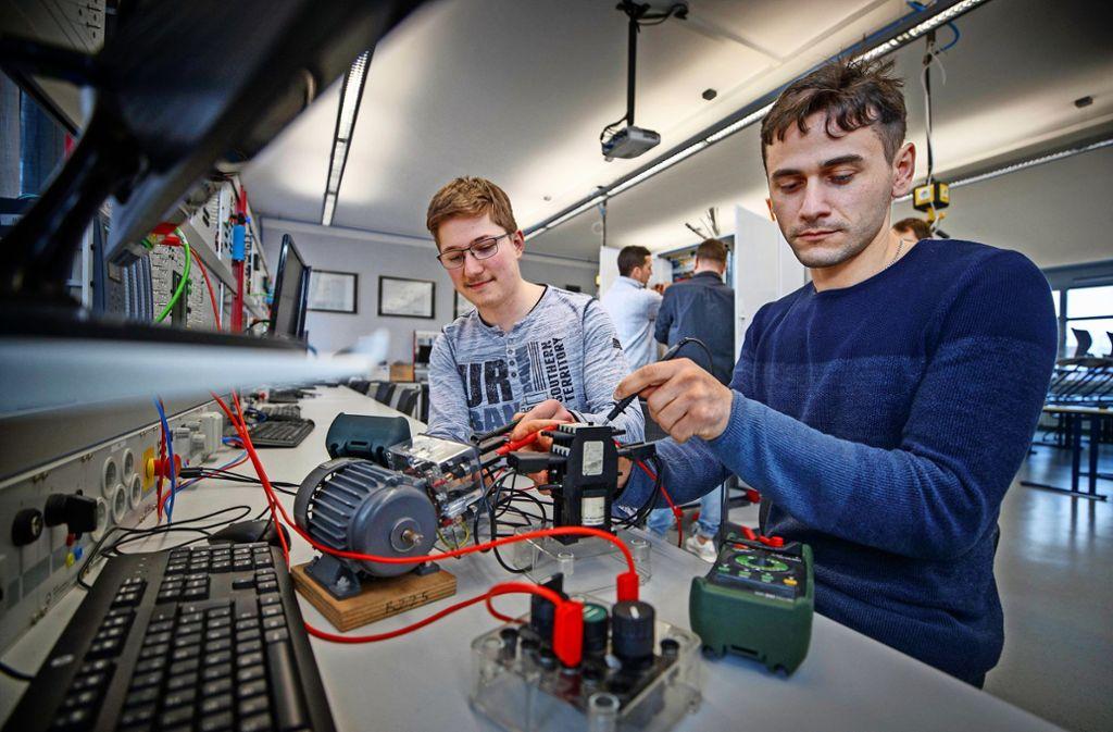 Jens Weller (links) und David Kokhodze im Labor. Dahinter arbeiten ihre Kollegen Alexander Kiefer und Tobias Neuerer an einem Schaltschrank. Foto: Gottfried Stoppel