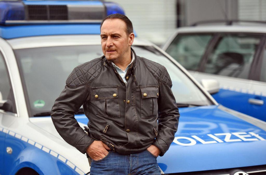 """Der Schauspieler Erdogan Atalay sitzt am  in Hürth (Nordrhein-Westfalen) bei einem Fototermin am Rande von Dreharbeiten zur RTL-Serie """"Alarm für Cobra 11"""" auf der Motorhaube eine Polizeiautos. Foto: dpa"""