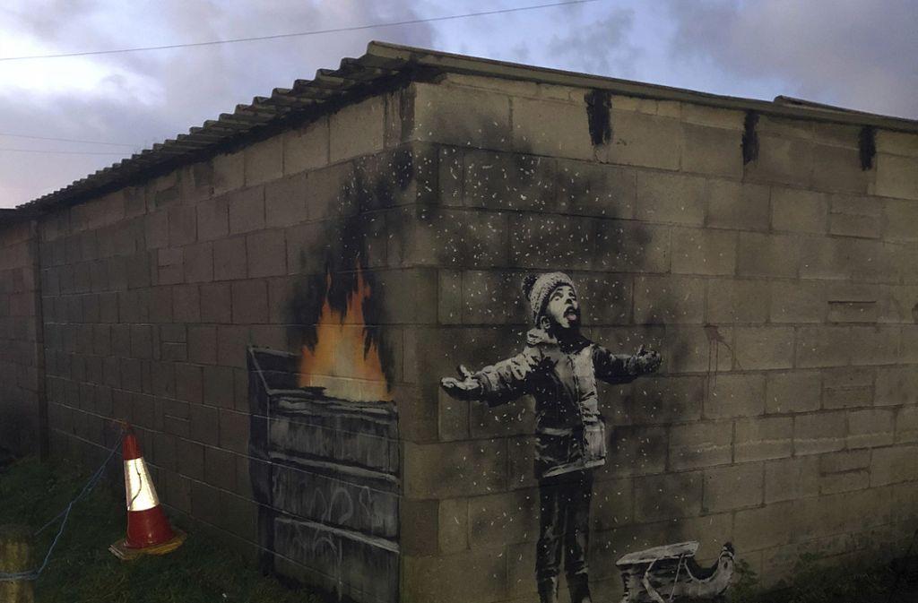 Ascheregen Auf einer Garage in Wales hat Banksy einen Jungen dargestellt, auf den Asche regnet. Auf der Instagram-Seite des Künstlers tauchte dazu ein Video auf, das die Echtheit des Bildes bestätigen sollte.  Foto: AP