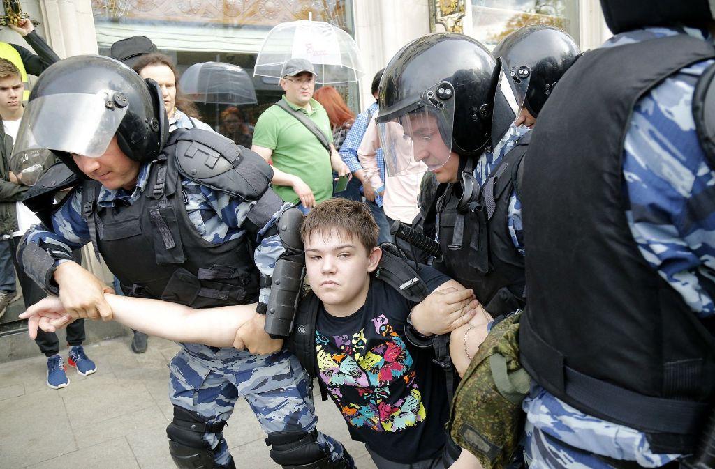 Polizisten nehmen während einer Antikorruptions-Demonstration in Moskau einen jungen Demonstranten fest. Foto: AP
