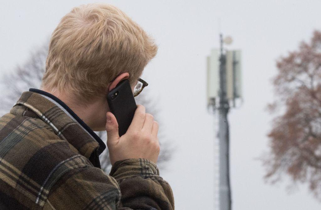 Ein Mann telefoniert neben einer Basisstation. Der Aufbau von Mobilfunkmasten  wird immer wieder gestoppt. Allein bei Vodafone gibt es bundesweit derzeit 562 Baustopps. Foto: dpa/Julian Stratenschulte