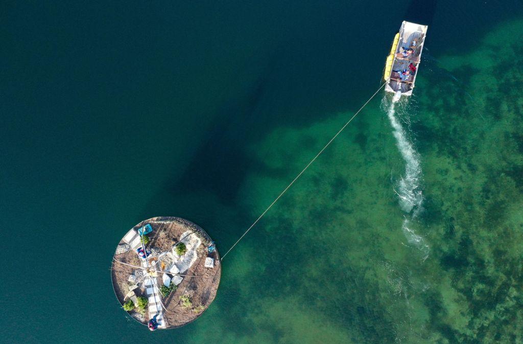 Die Arbeiten laufen auf Hochtouren. Ein Arbeitsboot schiebt einen schwimmenden Garten vor dem Überlinger Gartenschaugelände in Position. Foto: dpa/Felix Kästle