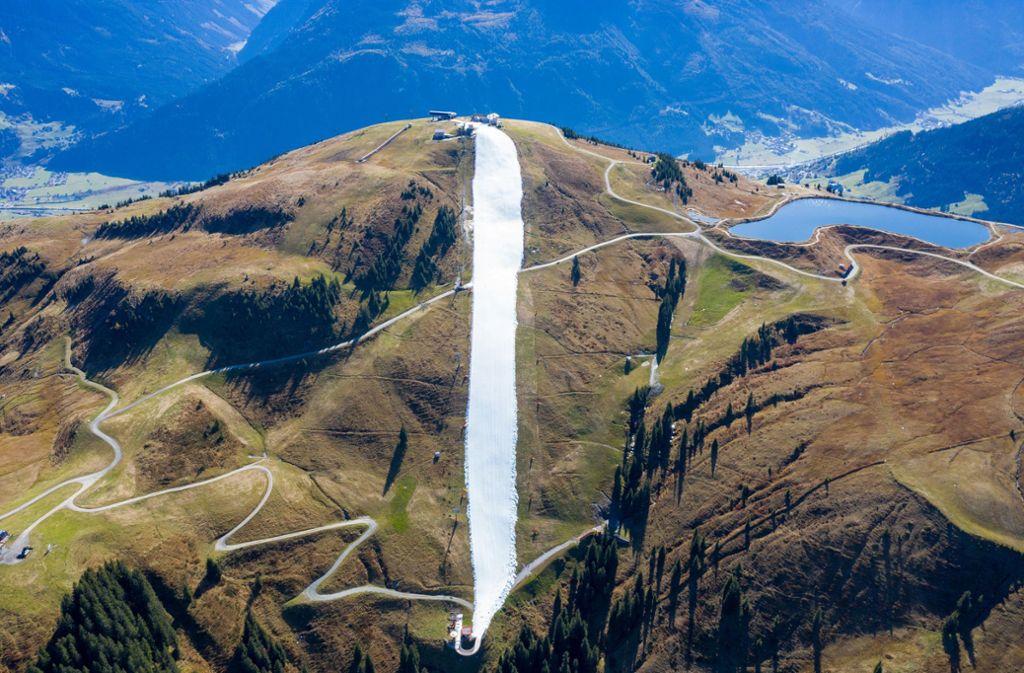 Für eine schmale Piste wurde konservierter Schnee aus dem vergangenen Winter als Band in der Berglandschaft auf der noch grünen Resterhöhe in den Kitzbüheler Alpen aufgetragen. Foto: dpa/Expa