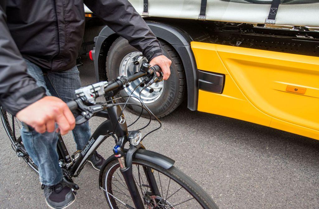 Ein Fahrradfahrer fährt während einer Demonstration des neuen Abbiegeassistenten neben einem Lastwagen. In dem kleinen schwarzen Kasten am Lkw befindet sich das neuartige Radarsystem. Foto: ZB/dpa