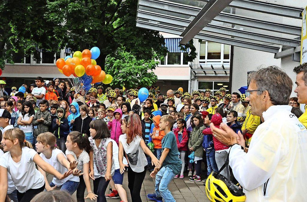 Der Empfang auf dem Schulhof am Fliegenweg wurde dank der Kinder zu einem fröhlichen ersten Tour-Gipfel. Dafür gab's von Bürgermeister Werner Wölfle (2.v.r.) Beifall. Foto: gli