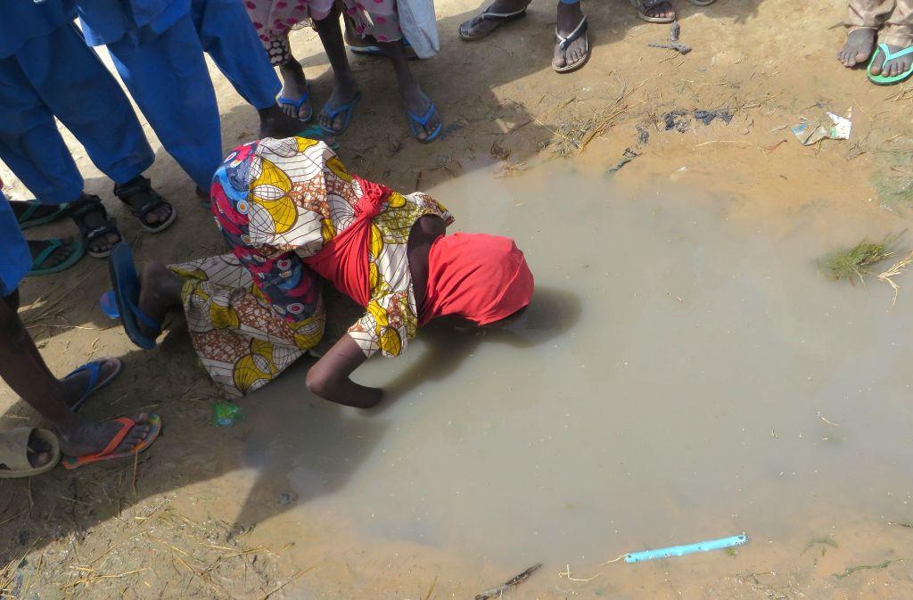 Ein durstiges Mädchen trinkt im Lager Muna Garage in Maiduguri, Nigeria, aus einer verdreckten Pfütze Wasser. Foto: dpa