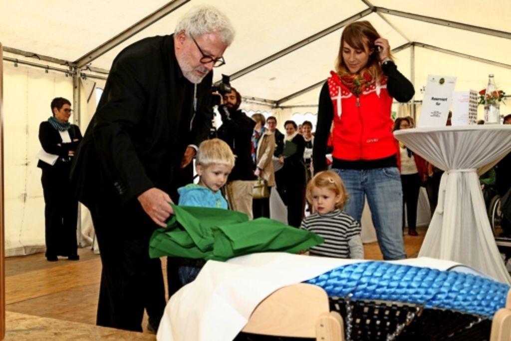 Die Kita-Kinder dürfen das Geschenk von Staatssekretär Klaus-Peter Murawski selbst auspacken: eine Vogelnestschaukel. Foto: Konzept-e/Perper